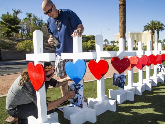 Sherri Camperchioli and Jordan Cassel, volunteers from Las Vegas, staple photos of the mass shooting victims on 58 crosses artist Greg Zanis of Aurora, Illinois, constructed.  He drove across the country, arriving in Las Vegas Thursday afternoon, Oct. 5, 2017, to install them on Las Vegas Blvd to honor the people killed in the mass shooting. Zanis said he has created crosses for many of the recent national tragedies, Newtown, San Bernardino and now Las Vegas. Mandalay Bay is in the background.