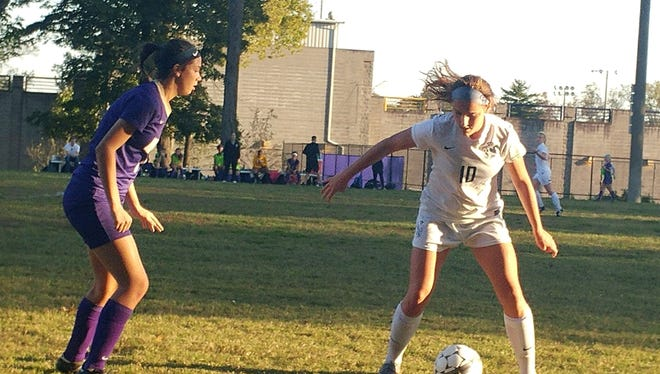 Sacred Heart senior Cassie Amshoff keeps a defender at bay during the first half of the Valkyries' 3-1 win over the Bulldogs in Seventh Region Tournament semifinals