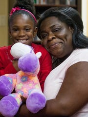 Christa Bumpers hugs her daughter Amanda as children are given gifts during Christmas in July at the Nellie Burge Community Center in Montgomery, Ala., on Saturday July 30, 2016.