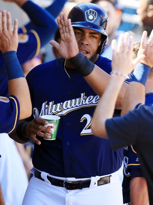 Jesús Aguilar is greeted by his Brewers teammates in the dugout after scoring during a spring training game Monday.