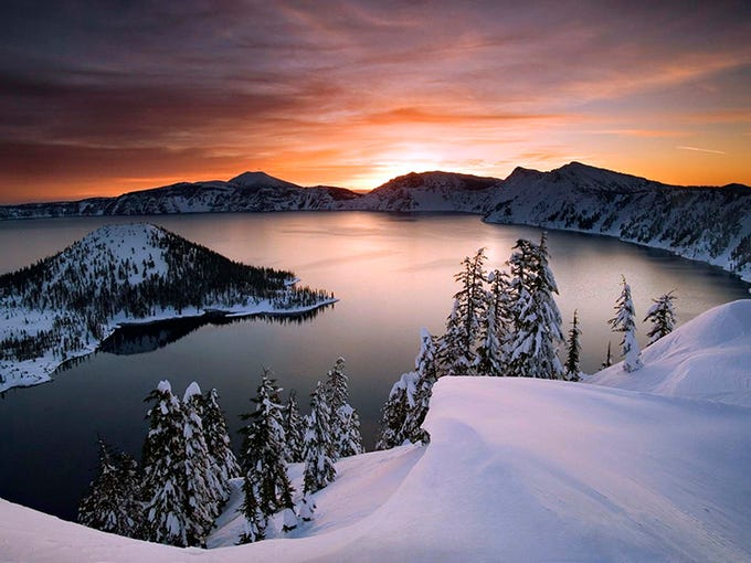 ,FILE - In this January 2006, file photo, the sun rises over Crater Lake, Ore., in Crater Lake National Park. Crater Lake lies in the caldera of an ancient volcano called Mount Mazama that collapsed 7,700 years ago, according the the National Parks Service. It is the deepest lake in the United States and is famous for its vivid blue color and water clarity.