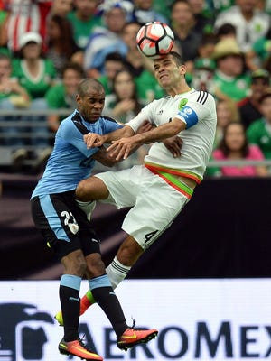 Mexico's Rafael Marquez (4) and Uruguay's Diego Rolan (22) go up for a header Sunday in Glendale, Ariz.