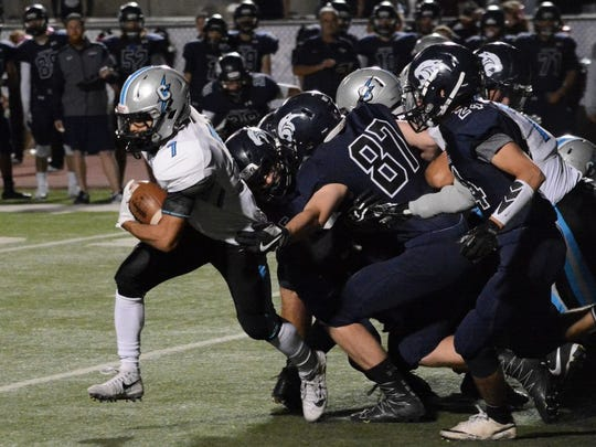 Cleveland running back Isaac Torres, center, breaks a tackle and picks up some extra yards against Piedra Vista during the first quarter of Friday's District 1-6A game at Hutchison Stadium.