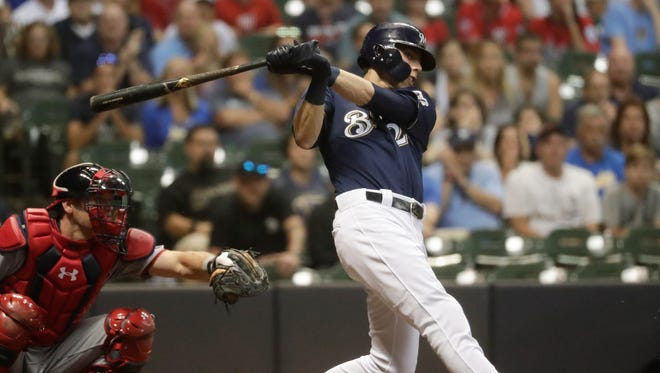 Christian Yelich hits a three-run triple during the sixth inning Monday night at Miller Park.