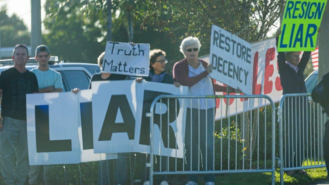 Trump protesters watch the Presidential motorcade drive by on Southern Blvd., in West Palm Beach on Sunday, January 5, 2020.