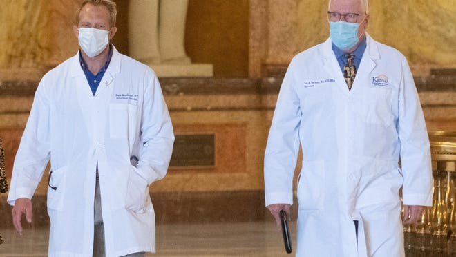 Lee Norman, right, Kansas secretary of health and environment, walks alongside Dana Hawkinson, with the University of Kansas Health Systems infectious diseases unit, before a press conference Wednesday at the Statehouse.
