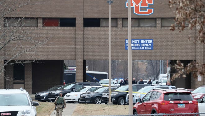 Police walk around the perimeter at Marshall County High School after a gunman opened fire. Two were killed and 17 more people were injured.  January 23, 2018