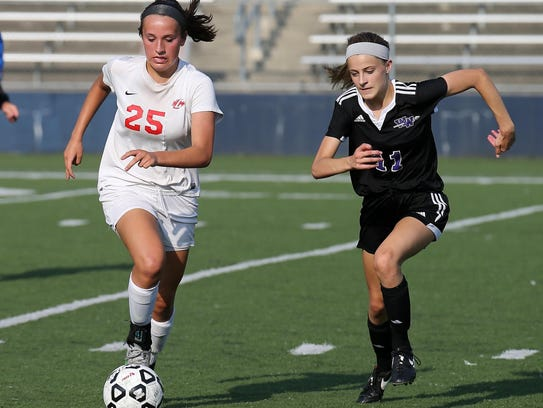 Canton's Hannah Lapko (left) maintains a step on Woodhaven's