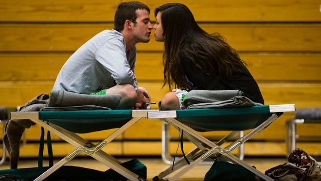 Nathan Westerfield, 22, kisses his new bride, Mickella, 20, at the Red Cross shelter set up at Sinagua Middle School in Flagstaff, Tuesday night, May 20,2014.  The couple, from Phoenix, who got married Sunday, were celebrating their honeymoon by camping out at Cave Springs campground in Oak Creek Canyon with equipment purchased with their wedding money.  They went into Sedona and were told they couldn't return after the Slide Fire broke out Tuesday afternoon.