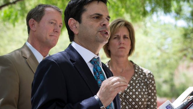 Phil Gordon (center), former Phoenix mayor and honorary chair for the Phoenix Citizens for Pension Responsibility, answers question during a press conference, June 10, 2014, at Cesar Chavez Plaza, 201 W. Washington Street.  Looking on are co-chairs for the Phoenix Citizens for Pension Responsibility Tom Simplot (left) and Cathy Gleason (right).