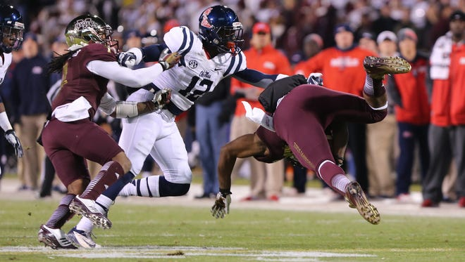 Mississippi State running back Josh Robinson is tripped up as he runs around right end in the first half as Ole MIss' Tony Conner (12) defends on the play. Mississippi State and Ole Miss played a college football game on November 28, 2013 at Davis Wade Stadium in Starkville. (Photo by Kevin Warren)