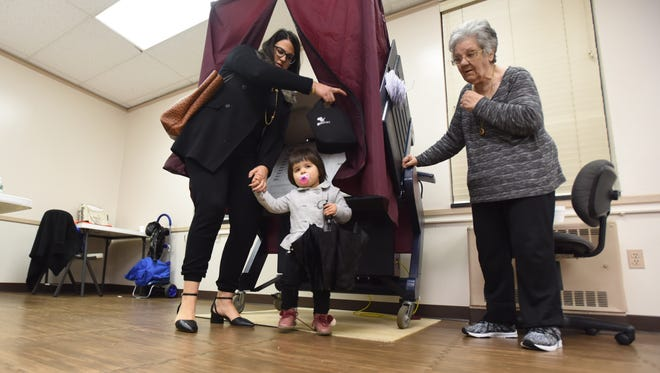 Elizabeth Borletti and her 2-year-old Estela exit the voting booth as poling worker Helen D'Antico looks on Election Day, Nov. 7, 2017.