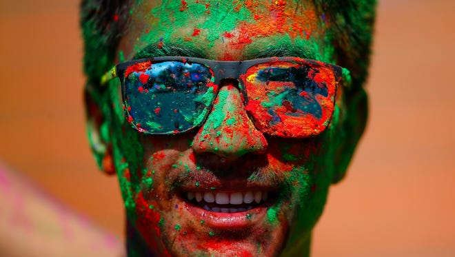A young man is covered in colored powder during celebrations of the Holi Festival in Kathmandu, Nepal.