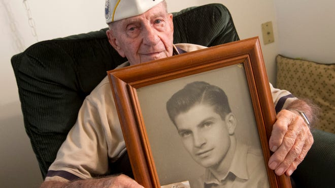 Orva Glass, who fought at Pearl Harbor on December 7, 1941, holds a portrait of himself taken a few weeks before the battle in Hawaii. Glass now lives in Lehigh Acres.