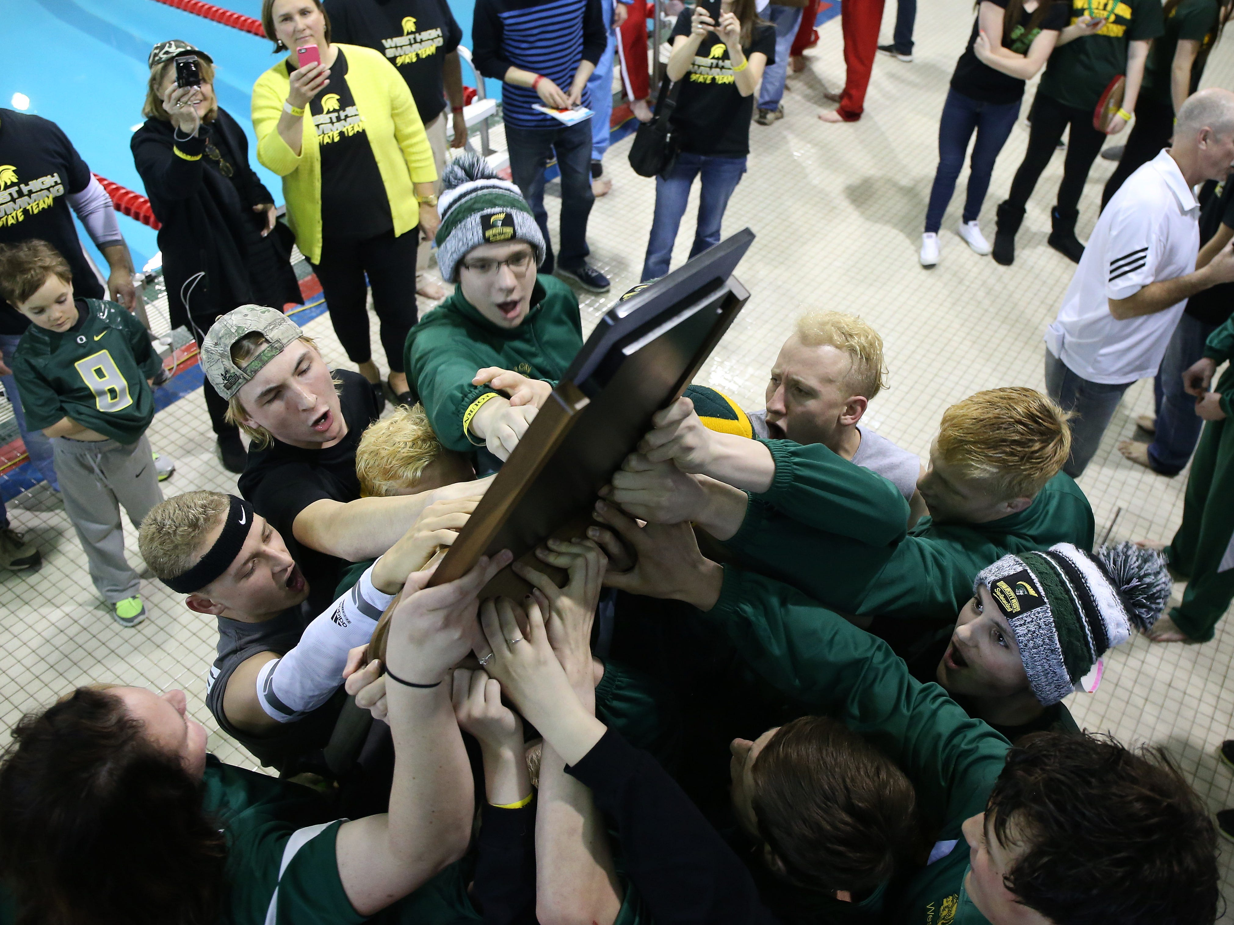 Members of the Iowa City West swim team celebrate after winning the state title on Saturday during the 2015 Iowa state boys' swim tournament in Marshalltown.