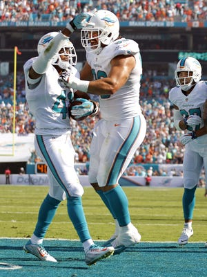 Miami Dolphins defensive back R.J. Stanford, left,  celebrates after intercepting the ball in the end zone Dec. 7, 2014.