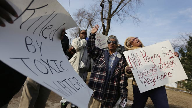 """""""We are tired and frustrated,"""" says Angela Hickmon of Flint, right during a rally where about 100 people demanded not to have to pay for water that is not fit for human consumption downtown Flint on Monday, January 25, 2016. """"The water is breaking me out. We are paying for something we can't use,"""" says Margie Scott, 71 of Flint, center."""