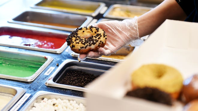 A freshly glazed doughnuts gets topped with chocolate chips on opening day at Fractured Prune Doughnuts Thursday, April 14, 2016, in the Shrewsbury Commons shopping center. The Shrewsbury store is the first in York County and the 36th for the Ocean City, Md.-based Fractured Prune Doughnuts, which CEO Dan Brinton said is opening 190 more stores nationwide. The Fractured Prune specializes in freshly fried doughnuts that are dipped in glazes and topped with sprinkles, sugar or other toppings, all to order. Local store owner Steve Hagee said he hopes to open additional stores in the York area as well as in Harrisburg.