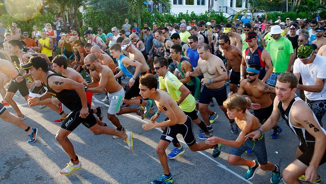 The first wave of runners cross the start line Sunday, June 7, 2015 at The Naples Beach Hotel & Golf Club. Hundreds of athletes competed in the 29th annual Fitness Challenge Triathlon. According to race director, Linda Hill Gregory of Y Not Tri, LLC, more than 600 individuals and 60 teams registered in a 3.1-mile run, 15K bike and .25-mile swim.