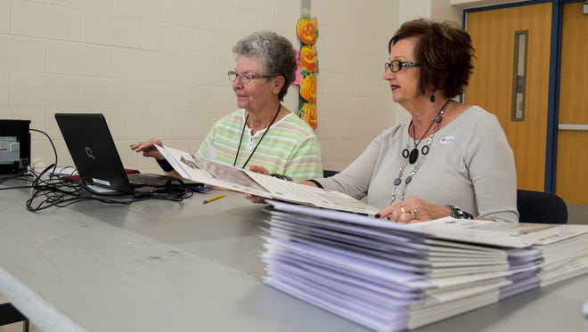 Joan Morrisson, left, and Saundra Heise work at Marysville's 3rd Precinct poll location at Marysville Gardens Elementary School, Tuesday, Nov. 7, 2017. According to local clerks, even though there is a shortage of poll workers, there are still enough to work the polls effectively.