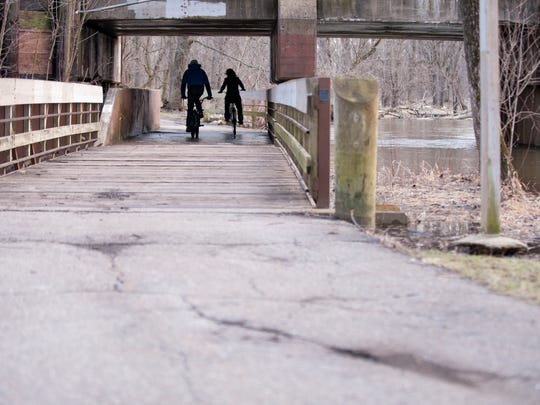 Bikers make their way along the Red Cedar River on the Lansing River Trail  on Tuesday, Various portions of the River Trail need updates. This particular section of the trail, from the railroad west of Interstate-496 to the connector to Fidelity Road has an estimated construction cost of $69,050.