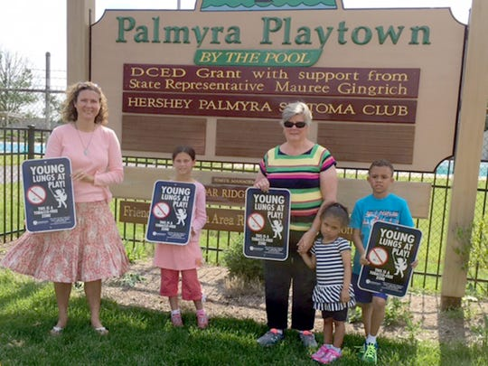 Pictured holding signs about the Young Lungs at Play initiative at Palmyra Playtown Park at the Palmyra Community Pool at 1122 Park Drive, Palmyra, are, from left, Holly Dolan, Lebanon Family Health Services; Abigail Dolan; Judy Ayle, president, Palmyra Recreation Association; Kaylee Hottenstein; and Trevor Hottenstein.