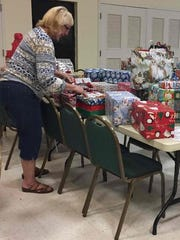 Pat Trickey was among nearly a dozen volunteers who sorted gifts on Dec. 22 at St. Luke's Episcopal Church fellowship hall in Port Salerno to ensure that they went to the right families in Indiantown.