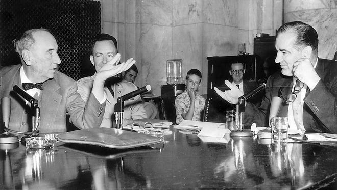 Sen. Joe McCarthy and Army counsel Joseph Welch say it with gestures during the celebrated hearings in Washington in June 1954. (AP)