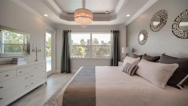 Thomasville pieces dominate the master bedroom, which features a leather headboard, footboard and rails. GHO Homes' 2,727-square-foot model home at Berkley Square in Vero Beach.