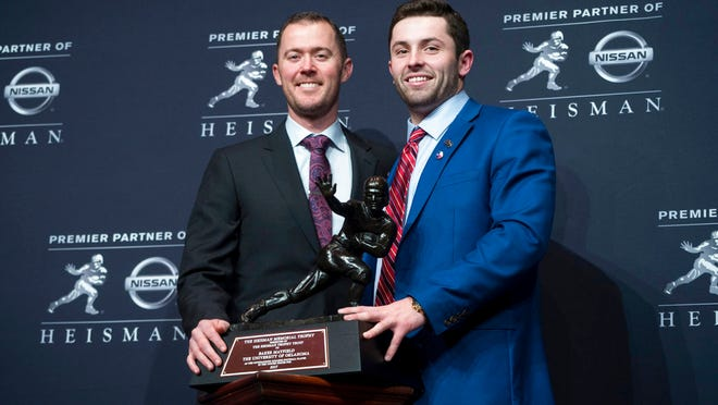 FILE - In this Dec. 9, 2017, file photo, Oklahoma head football coach Lincoln Riley, left, poses with Oklahoma quarterback Baker Mayfield, winner of the Heisman Trophy, during a news conference in New York. Oklahoma coach Lincoln Riley has been to the College Football Playoff twice and coached two Heisman winners since taking over as Oklahoma's coach 18 months ago. With all that success already at age 35, the school will have to battle to hold NFL teams at bay.