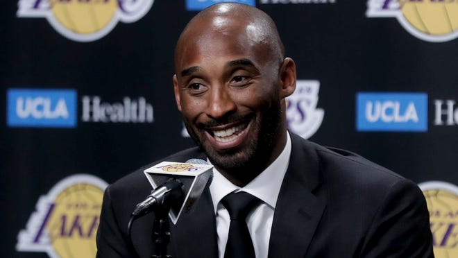 From Dec. 18, 2017, former Los Angeles Lakers standing Kobe Bryant talks during a news conference in Los Angeles.  Bryant and fellow NBA greats Tim Duncan and Kevin Garnett headlined a nine-person group announced Saturday, April 4, 2020,  as this year's class of enshrinees into the Naismith Memorial Basketball Hall of Fame. They all got into the Hall in their first year of eligibility, as did WNBA great Tamika Catchings. Two-time NBA champion coach Rudy Tomjanovich, longtime Baylor women's coach Kim Mulkey, 1,000-game winner Barbara Stevens of Bentley and three-time Final Four coach Eddie Sutton were selected. So was former FIBA Secretary General Patrick Baumann.