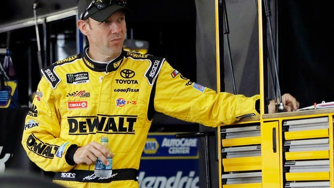 From July 29, 2017, Matt Kenseth stands in his garage stall after practice for a NASCAR Cup series auto race in Long Pond, Pa. At 48, Kenseth will be the oldest driver in the field when racing resumes.