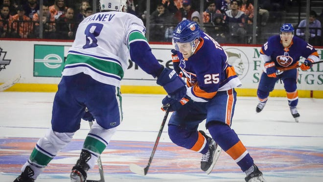 New York Islanders' Devon Toews (25) move puck around Vancouver Canucks defenseman Christopher Tanev (8) during an NHL hockey game, Saturday, Feb. 1, 2020, at Barclays Arena in New York.