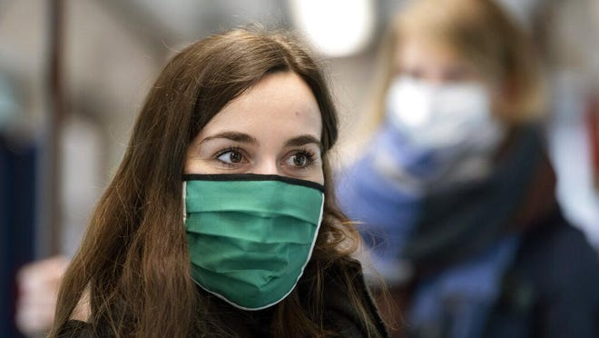 Women are wearing face masks in a tram during a presentation for journalists in Jena, Germany, Friday, April 3, 2020. Jena becomes first German city to make wearing a face mask mandatory. Starting at the beginning of next week, wearing a mouth and nose protection will be mandatory in Jena's shops, public transportation, and buildings with public access. For most people, the new coronavirus causes only mild or moderate symptoms, such as fever and cough. For some, especially older adults and people with existing health problems, it can cause more severe illness, including pneumonia.