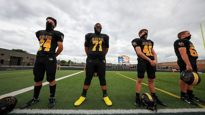 Members of the Upper Arlington football team stand for the national anthem before their season-opening game against Westerville Central on Aug. 28.