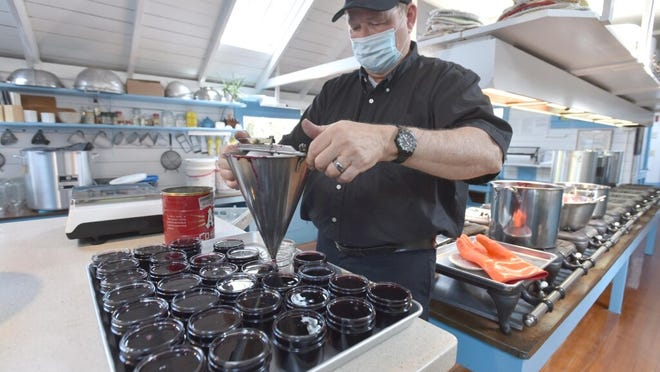 Ray Hebert, trustee chairman at the Cape Cod Museum of Natural History, uses a confectionery funnel to fill sterilized jars with beach plum jelly at the Greenbriar Jam Kitchen in Sandwich. In addition to supporting Greenbriar, planting a beach plum hedge at home could help your yard and the Cape's environment.