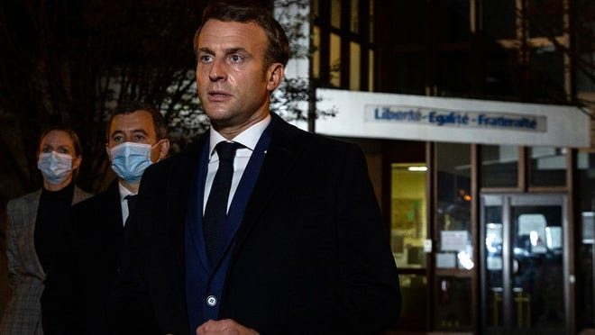 "French President Emmanuel Macron, flanked by French Interior Minister Gerald Darmanin, second left, speaks in front of a high school Friday Oct.16, 2020 in Conflans Sainte-Honorine, northwest of Paris, after a history teacher who opened a discussion with high school students on caricatures of Islam's Prophet Muhammad was beheaded. French President Emmanuel Macron denounced what he called an ""Islamist terrorist attack"" against a history teacher decapitated in a Paris suburb Friday, urging the nation to stand united against extremism."