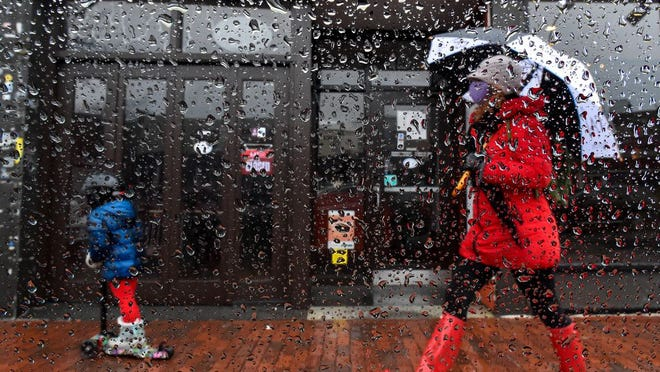A child rides a scooter and a woman holds an umbrella as they make their way through Davis Square in the rain on Monday, April 27, 2020.