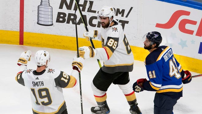St. Louis Blues' Robert Bortuzzo (41) looks on as Vegas Golden Knights' Reilly Smith (19) and teammate Alex Tuch (89) celebrate a goal during the second period of an NHL hockey playoff game Thursday, Aug. 6, 2020, in Edmonton, Alberta.