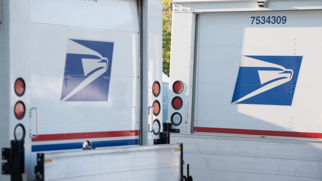 Postal trucks are parked at a United States Postal Service post office location in Washington, D.C.