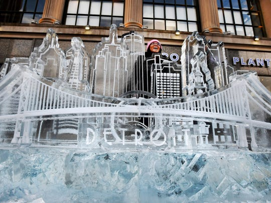 Detroiter Grace Albers braves frigid winds for a picture of the Detroit skyline created in ice at Winter Blast, which ends this weekend.
