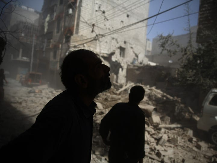Syrians look at the damage following air strikes on