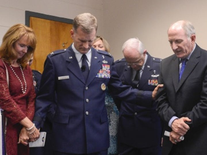 Col. Dondi Costin, second from left, prays with his