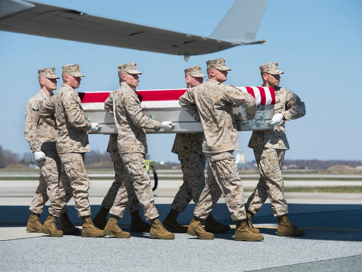 A Marine Corps carry team moves the remains of Staff