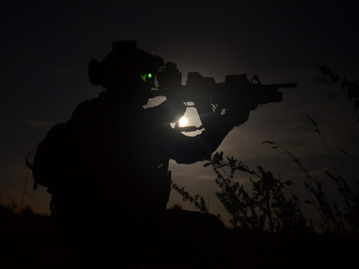 A special operations airman aims his weapon to designate