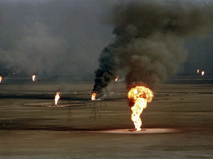An aerial view of burning oil wells damaged by retreating
