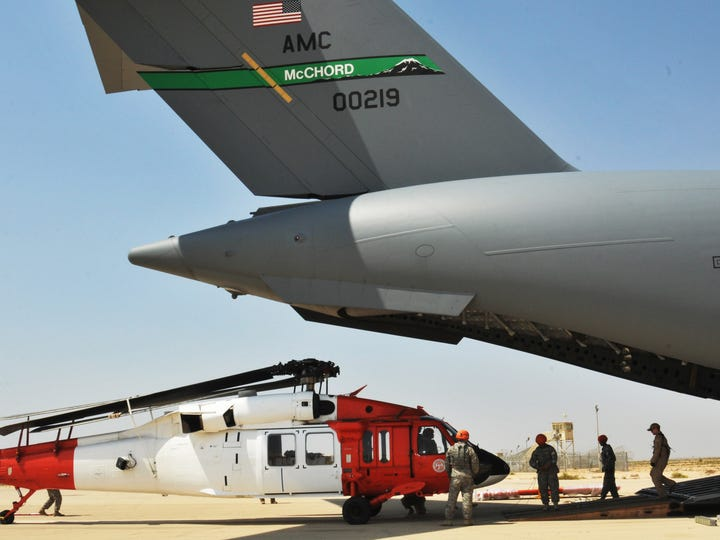 U.S. soldiers and airmen load a UH-60 Black Hawk into