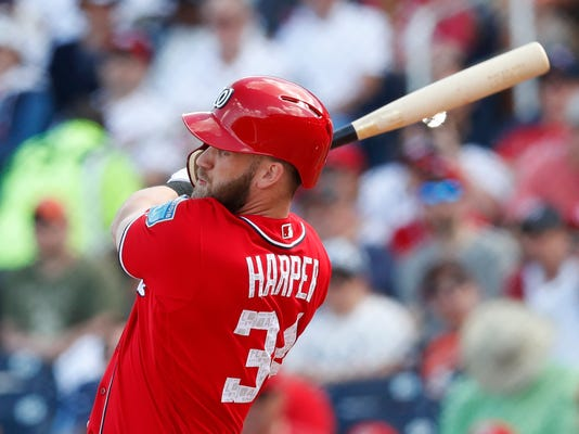 Washington Nationals' Bryce Harper (34) follows through on a two-run home run in the third inning of a spring training baseball game against the Detroit Tigers on Sunday, March 4, 2018, in West Palm Beach, Fla. (AP Photo/John Bazemore)