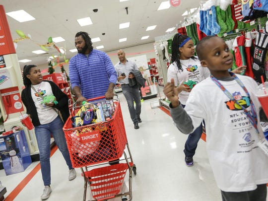 Brandon Pettigrew walks with Tiyanna Moore, left, Ja'Nae Walden, upper right, and Elijah Eigbokhan, lower right, while treating six children to a shopping spree in Dearborn on Tuesday.