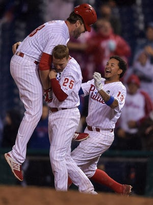 Darin Ruf of the Philadelphia Phillies jumps into the arms of Cody Asche and Freddy Galvis after hitting a walk-off single in the ninth inning against the Cincinnati Reds.